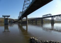 From the eastern bank of the Peace River, the new piers await arrival of the deck
