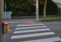 Swarco's SafeLight shines a red light down to the pavement next to the traffic light pole