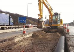 A New Holland E235B reduced tailswing tracked excavator at work on the motorway